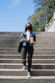 Portret van een jonge vrouw die een gezichtsmasker draagt en haar mobiele telefoon gebruikt tijdens het buiten lopen. nieuw normaal levensstijlconcept. stedelijk concept.