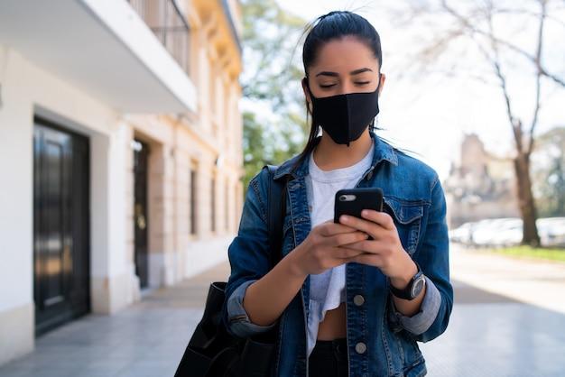 Portret van een jonge vrouw die een gezichtsmasker draagt en haar mobiele telefoon gebruikt tijdens het buiten lopen op straat. nieuw normaal levensstijlconcept. stedelijk concept.