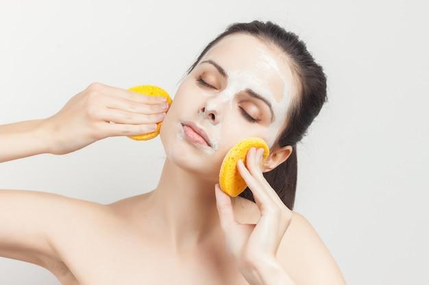 Portret van een jonge vrouw die een gezichtsmasker verwijdert