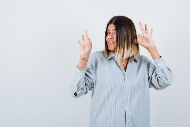 Portret van een jonge vrouw die een goed gebaar in een te groot shirt toont en er gelukkig vooraanzicht uitziet