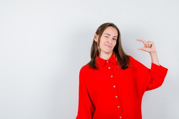 Portret van een jonge vrouw die een klein bordje laat zien terwijl ze in een rode blouse knippert en peinzend vooraanzicht kijkt