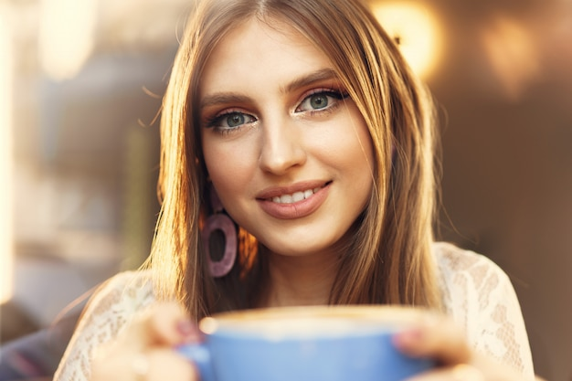 Portret van een jonge vrouw die een kop van koffie heeft en door het venster kijkt