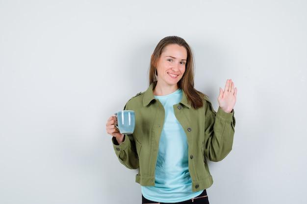 Portret van een jonge vrouw die een kopje drank vasthoudt, groet met open hand in t-shirt, jas en vrolijk vooraanzicht