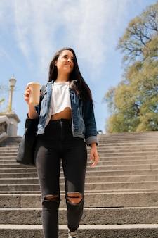 Portret van een jonge vrouw die een kopje koffie vasthoudt terwijl ze buiten loopt. stedelijk begrip.