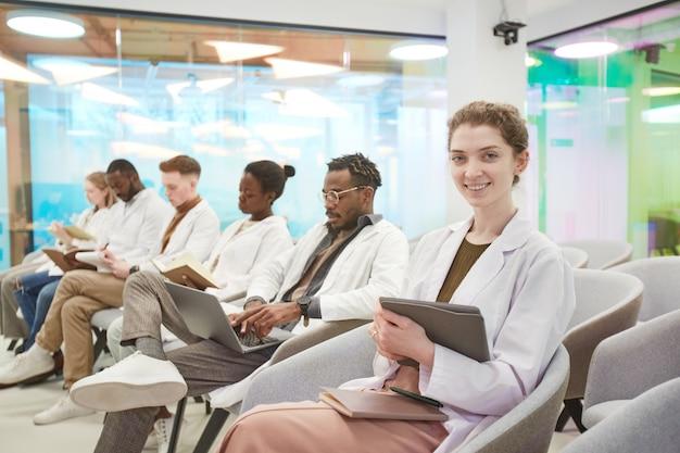 Portret van een jonge vrouw die een laboratoriumjas draagt en naar de camera glimlacht terwijl ze in de rij zit met een multi-etnische groep mensen in het publiek tijdens een medisch seminar, kopieer ruimte