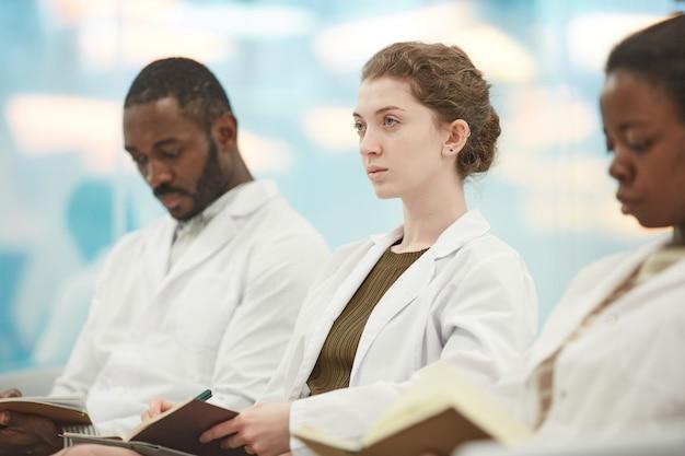 Portret van een jonge vrouw die een laboratoriumjas draagt terwijl ze in de rij zit met mensen in het publiek en luistert naar een lezing over geneeskunde op de universiteit, kopieer ruimte