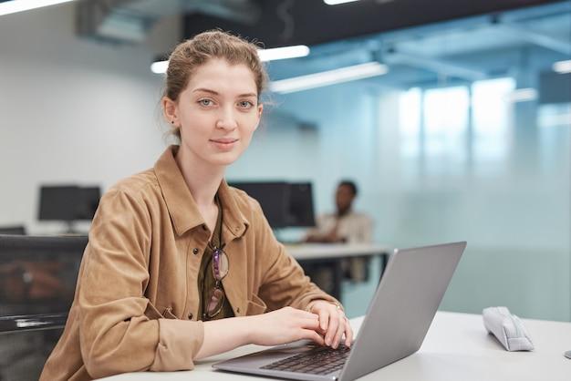 Portret van een jonge vrouw die een laptop gebruikt om te glimlachen naar de camera in een kantoor- of schoolbibliotheek, kopieer ruimte