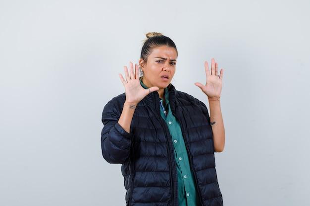 Portret van een jonge vrouw die een overgavegebaar toont in een overhemd, een pufferjack en een bang vooraanzicht