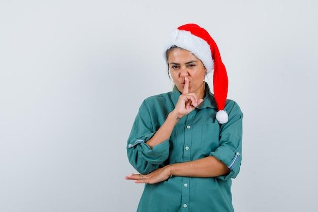 Portret van een jonge vrouw die een stiltegebaar in een shirt, een kerstmuts en een zelfverzekerd vooraanzicht toont