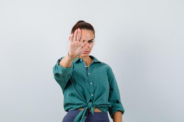 Portret van een jonge vrouw die een stopgebaar in een groen shirt toont en er een geïrriteerd vooraanzicht uitziet