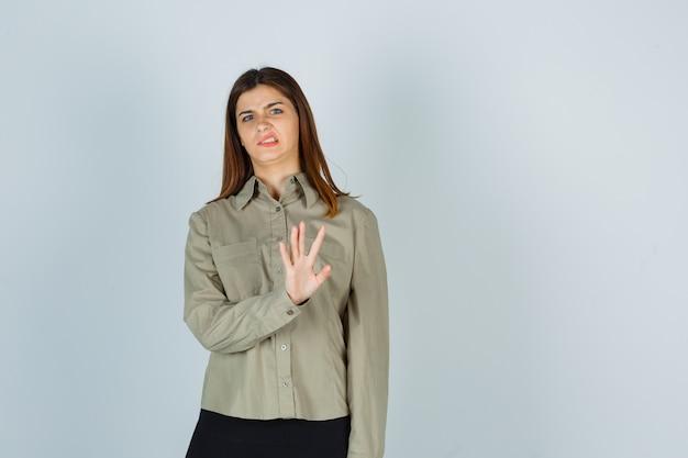 Portret van een jonge vrouw die een stopgebaar toont, fronsend van ongenoegen in shirt, rok en walgelijk vooraanzicht