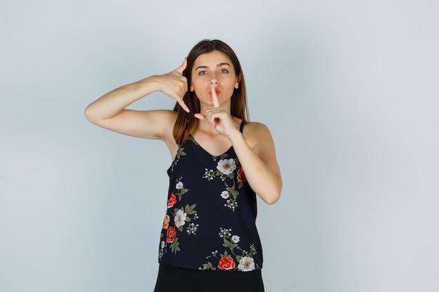 Portret van een jonge vrouw die een telefoongebaar en een stilteteken toont in blouse, rok en zorgvuldig vooraanzicht kijkt