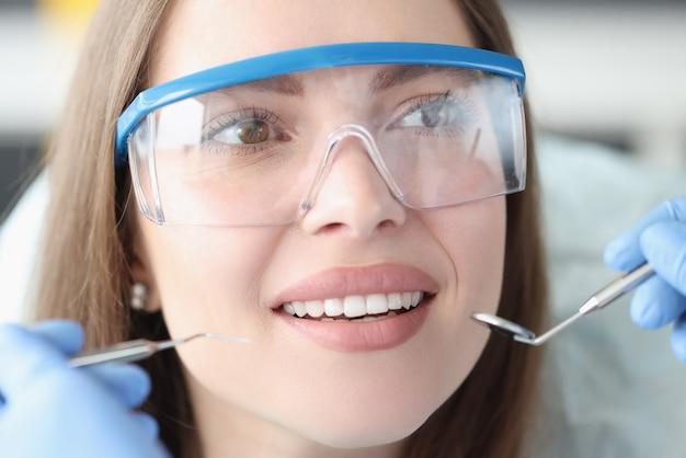 Portret van een jonge vrouw die een veiligheidsbril draagt bij een tandartsafspraak