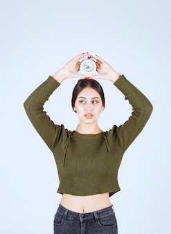 Portret van een jonge vrouw die een wekker vasthoudt met een serieuze uitdrukking.