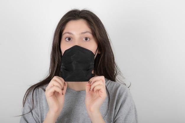 Portret van een jonge vrouw die een zwart gezichtsmasker op wit draagt.