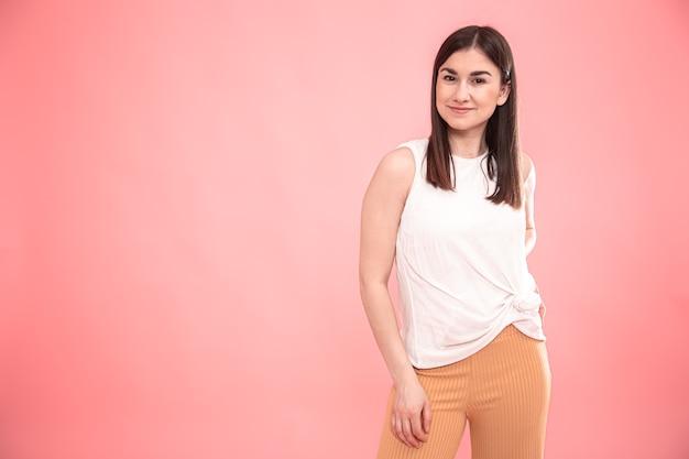 Portret van een jonge vrouw die emoties op een geïsoleerde roze achtergrond toont.