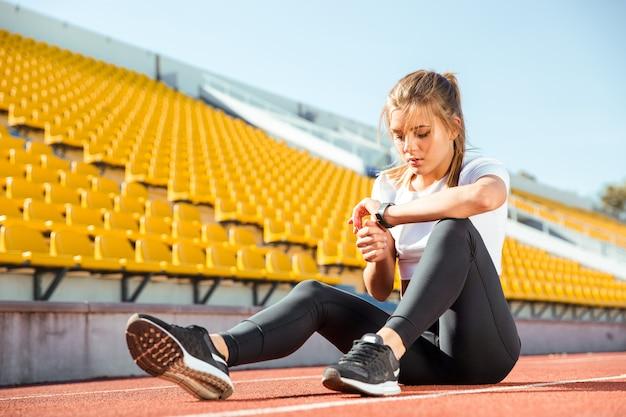 Portret van een jonge vrouw die en op polshorloge bij stadion rusten kijkt