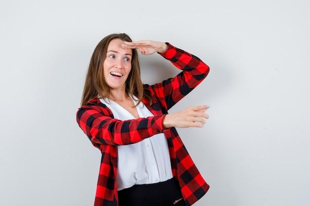 Portret van een jonge vrouw die ergens wijst, ver weg kijkt met de hand boven het hoofd in vrijetijdskleding en een verbaasd vooraanzicht kijkt