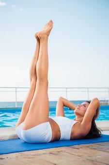 Portret van een jonge vrouw die fitnessoefeningen buiten in de ochtend maakt