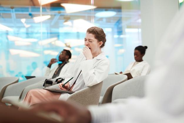 Portret van een jonge vrouw die gaapt terwijl ze in het publiek zit en luistert naar een lezing over medicijnen op de universiteit of een coworkingcentrum, kopieer ruimte
