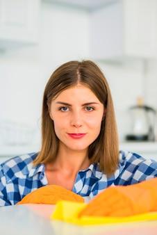 Portret van een jonge vrouw die gele stofdoek op witte oppervlakte houdt