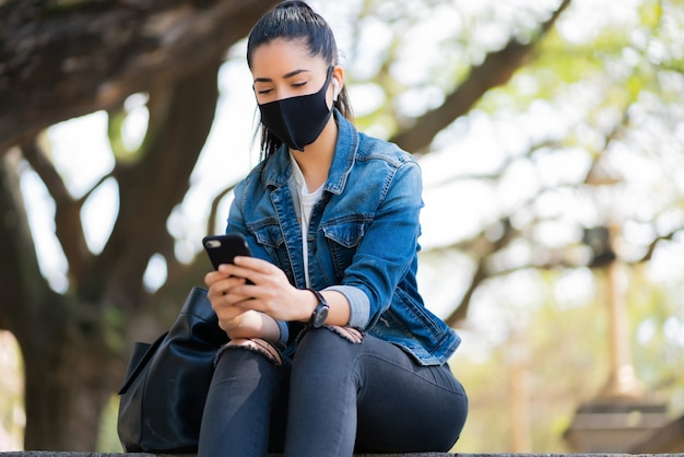 Portret van een jonge vrouw die gezichtsmasker draagt en haar mobiele telefoon gebruikt terwijl zij op treden buiten zit