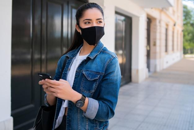 Portret van een jonge vrouw die gezichtsmasker draagt en haar mobiele telefoon gebruikt tijdens het buiten lopen op straat