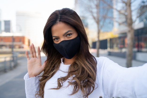 Portret van een jonge vrouw die gezichtsmasker draagt en selfies neemt terwijl de hand zwaait om buiten hallo te zeggen. stedelijk concept. nieuw normaal levensstijlconcept.
