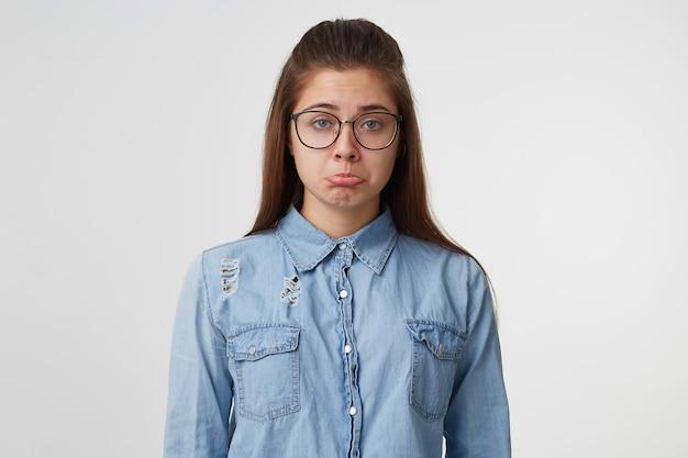 Portret van een jonge vrouw die glazen met lang haar draagt, gekleed in denimoverhemd