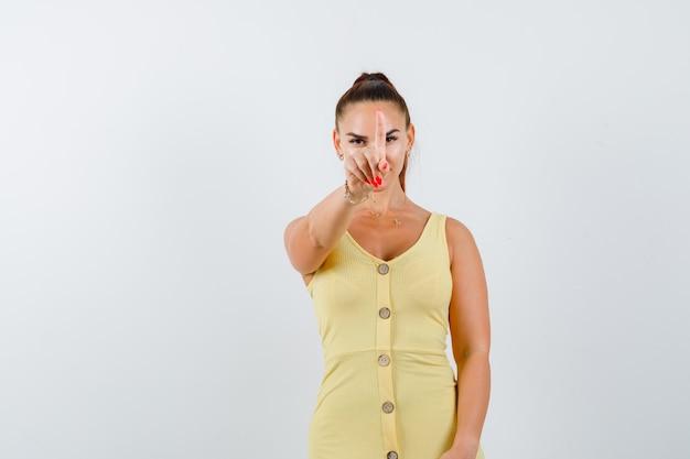 Portret van een jonge vrouw die greep op een minuutgebaar in gele kleding toont en zelfverzekerd vooraanzicht kijkt