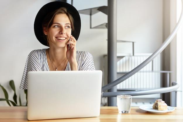 Portret van een jonge vrouw die grote hoed draagt en laptop met behulp van