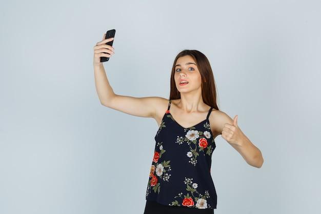 Portret van een jonge vrouw die haar duim opsteekt terwijl ze een selfie neemt op een smartphone in een blouse en er blij uitziet