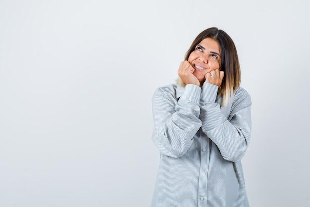Portret van een jonge vrouw die haar gezicht op handen in een oversized shirt dempt en er gelukkig vooraanzicht uitziet