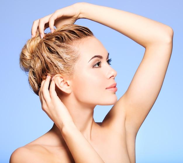 Portret van een jonge vrouw die haar haar op een blauwe muur wast