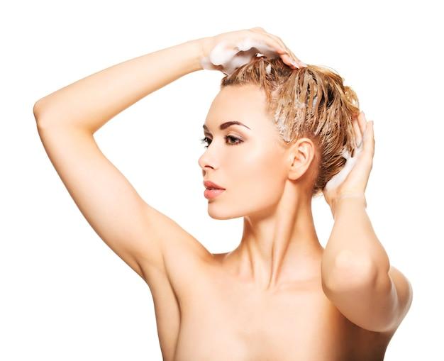 Portret van een jonge vrouw die haar haar op een wit wast