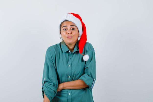 Portret van een jonge vrouw die haar hand op de buik houdt in een shirt, een kerstmuts en een verbaasd vooraanzicht kijkt