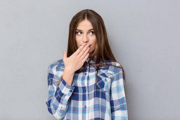 Portret van een jonge vrouw die haar mond bedekt met handpalm en wegkijkt over een grijze muur