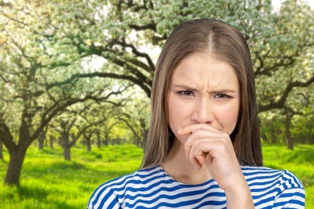 Portret van een jonge vrouw die haar neus houdt