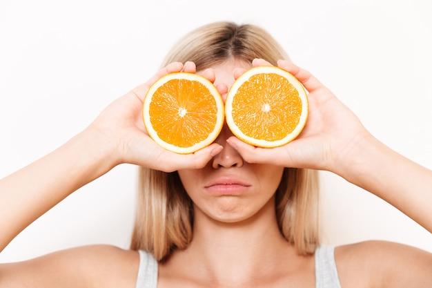 Portret van een jonge vrouw die haar ogen met oranje fruit