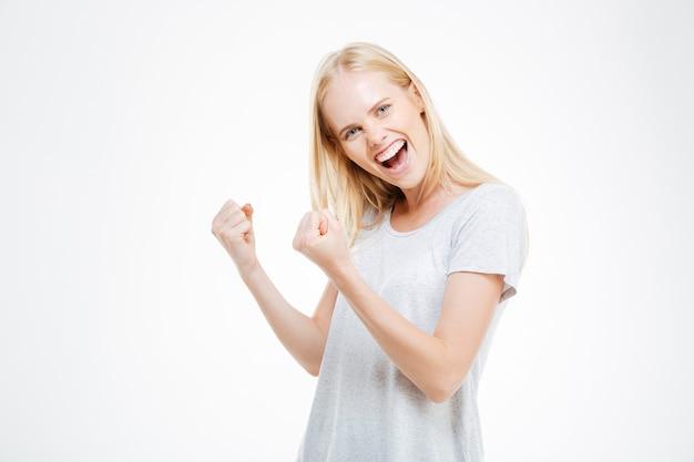 Portret van een jonge vrouw die haar succes viert dat op een witte achtergrond wordt geïsoleerd