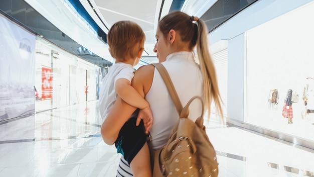 Portret van een jonge vrouw die haar zoontje knuffelt en in een groot winkelcentrum loopt