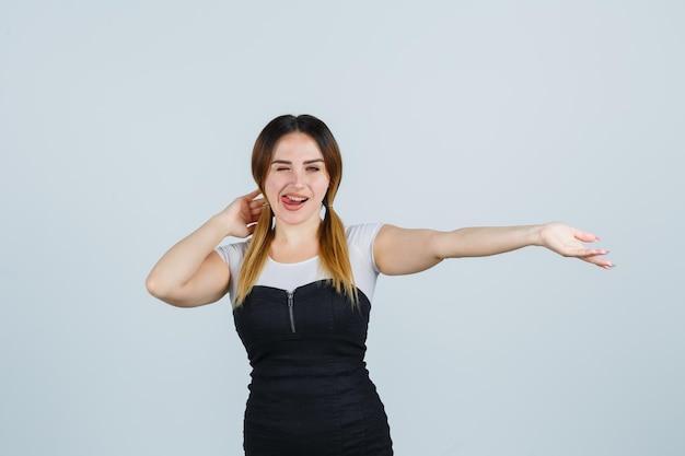 Portret van een jonge vrouw die hand achter het hoofd houdt en tong uitsteekt