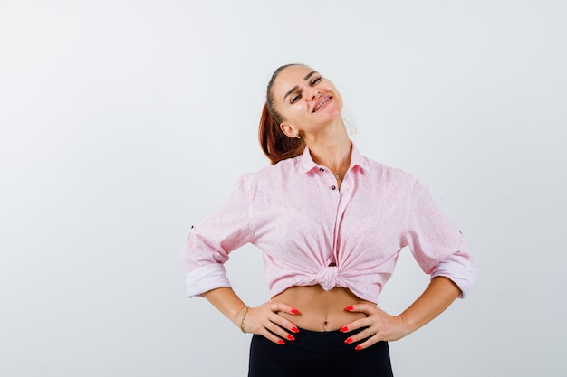 Portret van een jonge vrouw die hand op heup in casual shirt houdt en aantrekkelijk vooraanzicht kijkt
