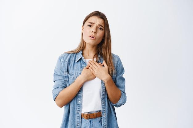 Portret van een jonge vrouw die handen op het hart houdt en naar iets schattigs en moois kijkt, zich ontroerd en oprecht voelt, staande over een witte muur