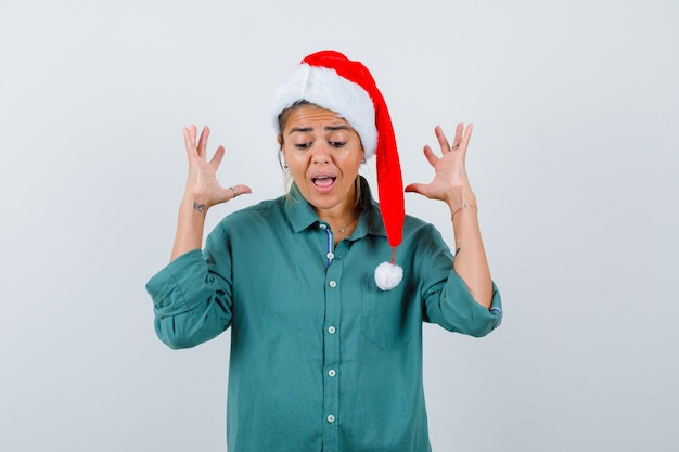 Portret van een jonge vrouw die handen opsteekt terwijl ze schreeuwt in shirt, kerstmanhoed en met afschuw vervuld vooraanzicht kijkt