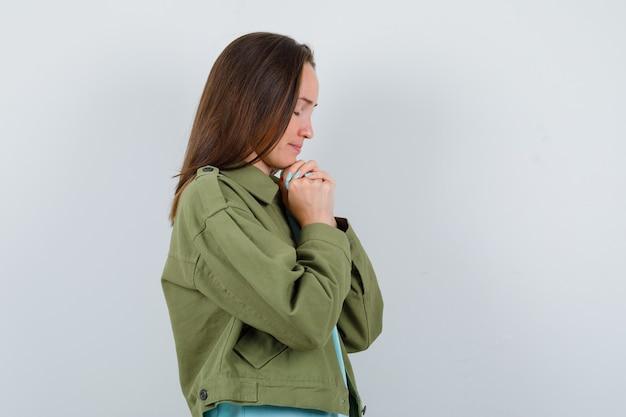 Portret van een jonge vrouw die handen vastgrijpt in een biddend gebaar in een groen jasje en er hoopvol uitziet?