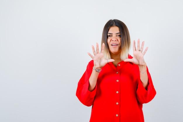 Portret van een jonge vrouw die handpalmen in een rood oversized shirt toont en er mooi vooraanzicht uitziet Premium Foto