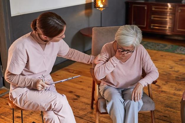 Portret van een jonge vrouw die huilende senior dame troost tijdens therapiesessie in bejaardentehuis, kopieer ruimte
