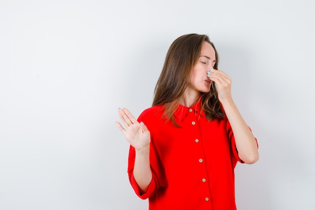 Portret van een jonge vrouw die iets vreselijks ruikt, neus knijpt, stopbord in rode blouse laat zien en walgelijk vooraanzicht kijkt