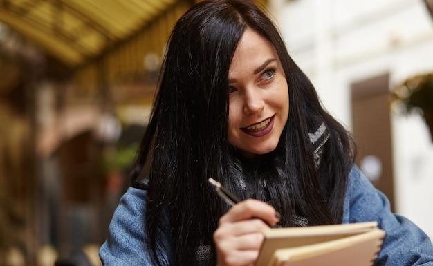Portret van een jonge vrouw die in café met pen zit